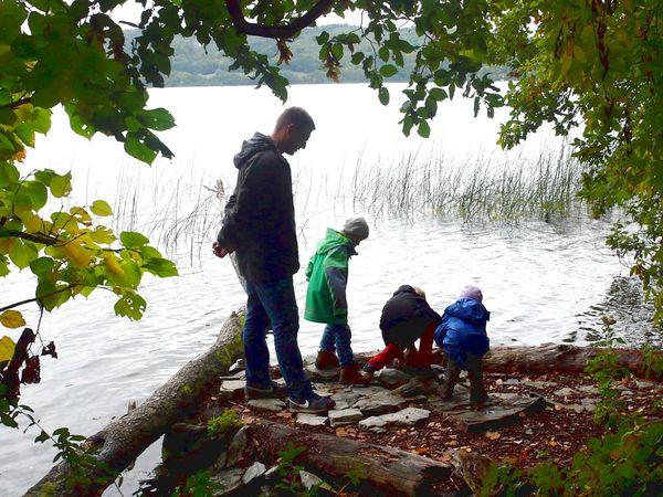 Kinder beobachten die Blasen im Laacher See
